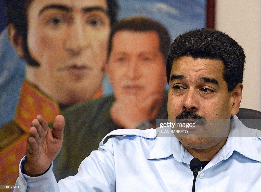 Venezuelan president Nicolas Maduro speaks in front of a painting depicting late president Hugo Chavez (C) and Latin American independence hero Simon Bolivar, during a press conference in Caracas on November 15, 2013. Venezuela's legislature gave initial backing Thursday to a measure granting extraordinary powers over the economy to President Nicolas Maduro, following his controversial attempt to forcibly cut consumer prices. Maduro's supporters, who hold the majority in the National Assembly, approved the measure which would allow him to govern by decree, without having to seek parliamentary approval. AFP PHOTO/JUAN BARRETO