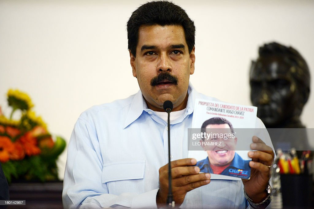 Venezuelan President Nicolas Maduro talks and shows a brochure with the portrait of late President Hugo Chavez during a press conference at the Miraflores Presidential Palace in Caracas on September 09, 2013. Venezuela on Tuesday will leave the Inter American Human Rights Court. AFP PHOTO/ Leo RAMIREZ.