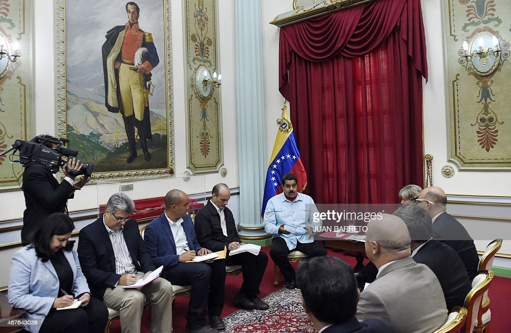 Venezuelan President Nicolas Maduro (C) talks with the Executive Secretary of the Economic Commission for Latin America and the Caribbean (UNECLAC), Alicia Barcena (R, partially covered), during a meeting in Caracas on March 26, 2015.