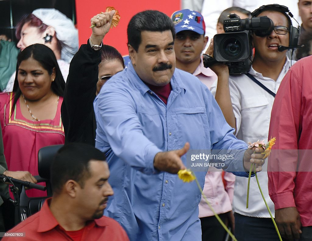 Venezuelan President Nicolas Maduro throws flowers during a rally with women in Caracas on May 24, 2016. / AFP / JUAN