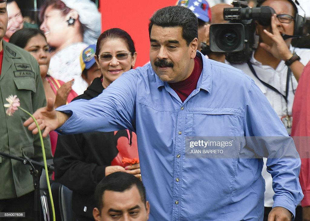 Venezuelan President Nicolas Maduro throws flowers next to First Lady Cilia Flores during a rally with women in Caracas on May 24, 2016. / AFP / JUAN