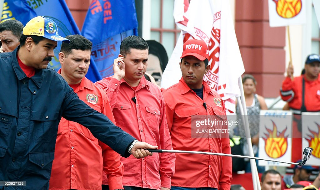 Venezuelan President Nicolas Maduro(L) uses a video camera during a march to mark International Workers' Day, in Caracas on May 1, 2016. / AFP / JUAN