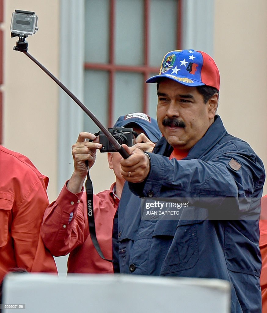 Venezuelan President Nicolas Maduro uses a video camera during a march to mark International Workers' Day, in Caracas on May 1, 2016. / AFP / JUAN