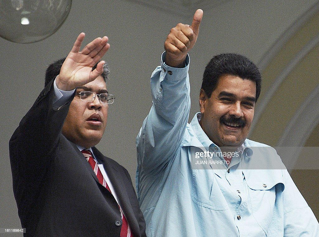 Venezuelan President Nicolas Maduro (R) waves after a meeting with Venezuela's Foreign Minister Elias Jaua, in Caracas on September 19, 2013. Jaua said Thursday that the United States didn't authorize the plane of President Maduro to fly across the Puerto Rican airspace on its way to China. AFP PHOTO/JUAN BARRETO