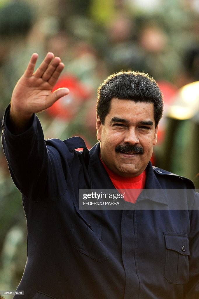 Venezuelan President Nicolas Maduro (C-L) waves as he arrives to the celebrations for the fifth anniversary of the Bolivarian Militia in Caracas on April 13, 2015. AFP PHOTO/FEDERICO PARRA