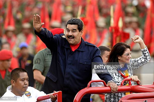 Venezuelan President Nicolas Maduro waves as he arrives with his wife Cilia Flores during the celebrations for the fifth anniversary of the...