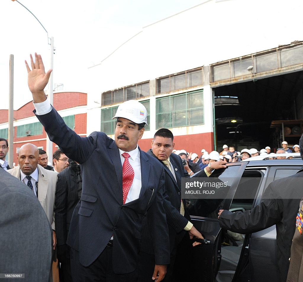 Venezuelan President Nicolas Maduro waves at the end of a visit to the Urutransfor factory in Montevideo, on May 7, 2013. Maduro visits Uruguay as part of a tour that also includes Argentina and Brazil. AFP PHOTO/Miguel ROJO