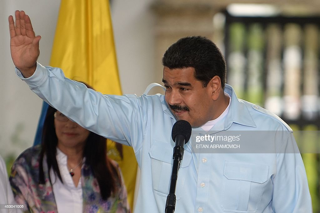 Venezuelan President Nicolas Maduro waves during a press conference with his Colombian counterpart Juan Manuel Santos during a meeting in Cartagena...