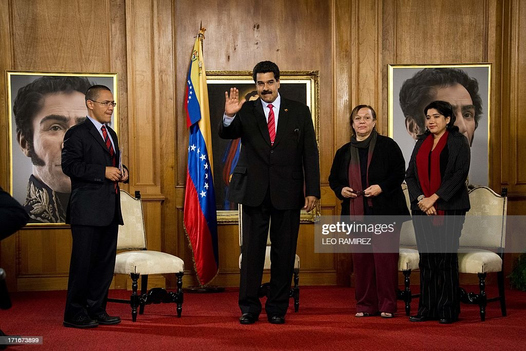 Venezuelan President Nicolas Maduro (C) waves next to Communication Minister, Ernesto Villegas (L) during the ceremony to posthumously grant former President Hugo Chavez the National Journalism award, at the Miraflores presidential palace in Caracas on June 27, 2013. AFP PHOTO/Leo RAMIREZ