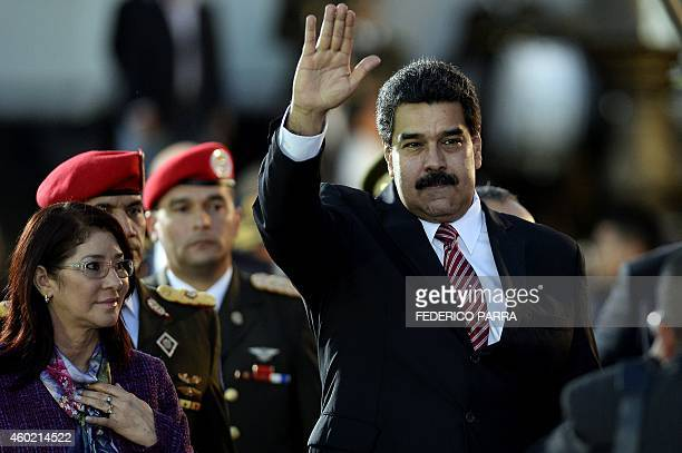Venezuelan President Nicolas Maduro waves next to First Lady Cilia Flores during the commemoration of the 190 years of the Battle of Ayacucho and...
