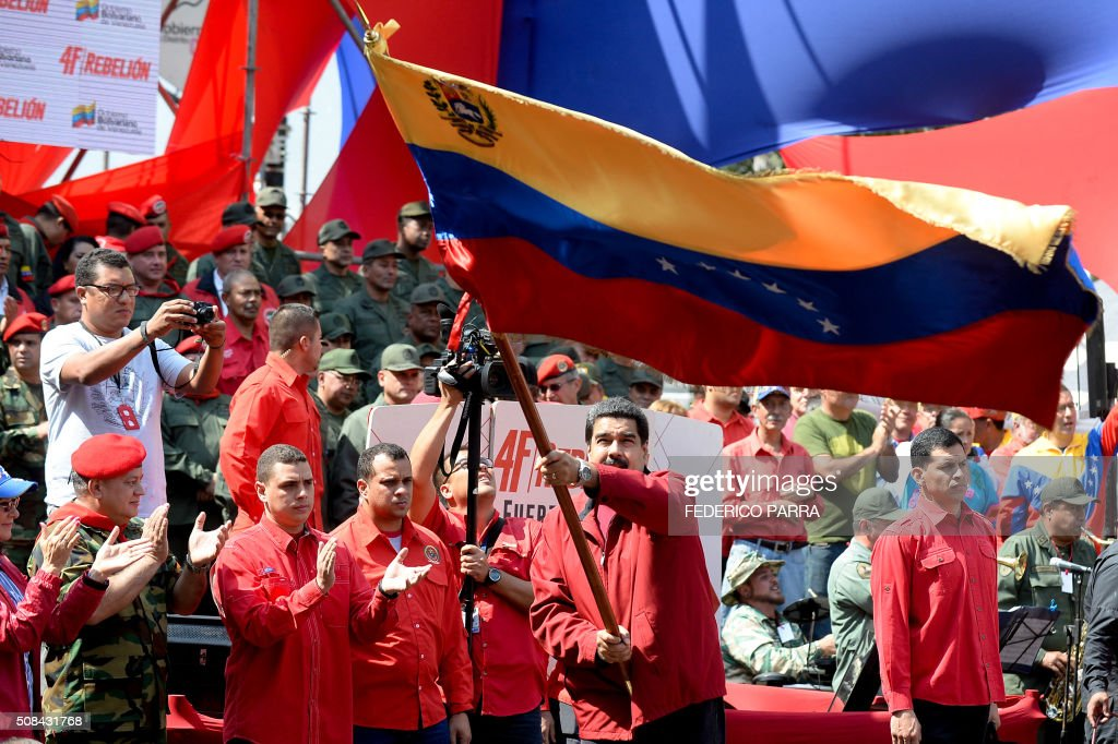 Venezuelan President Nicolas Maduro waves the national flag during a ceremony to commemorate the 24th anniversary of former Venezuelan President Hugo...
