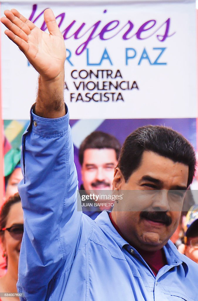 Venezuelan President Nicolas Maduro waves to supporters during a rally with women in Caracas on May 24, 2016. / AFP / JUAN