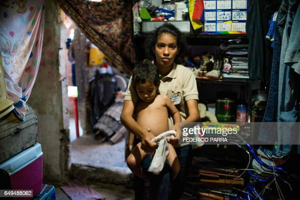 Venezuelan Rebeca Leon who scavanges for food in the streets of Caracas poses with her twoyearold son at her house in Petare shantytown on February...