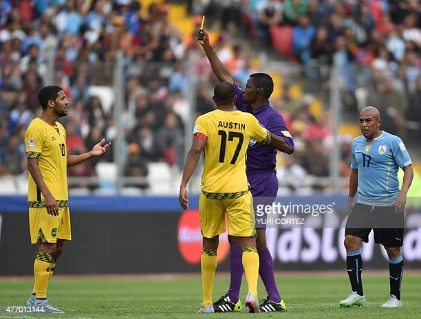 Venezuelan referee Jose Argote shows a yellow card to Jamaica's midfielder Joel McAnuff during their Copa America football match against Uruguay in...