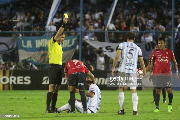 Venezuelan referee Juan Soto shows the yellow card to Bolivian Wilstermann Cristian Chavez during the Libertadores Cup football match against...