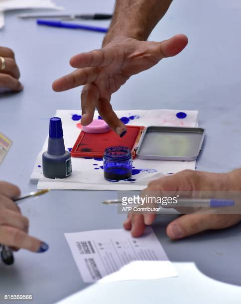 A Venezuelan resident in Madrid puts ink on his finger to stamp his fingerprint at a polling station during a symbolic plebiscite on president...