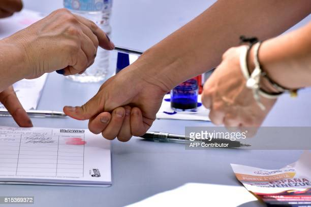 A Venezuelan resident in Madrid stamps fingerprint at a polling station during a symbolic plebiscite on president Maduro's project of a future...