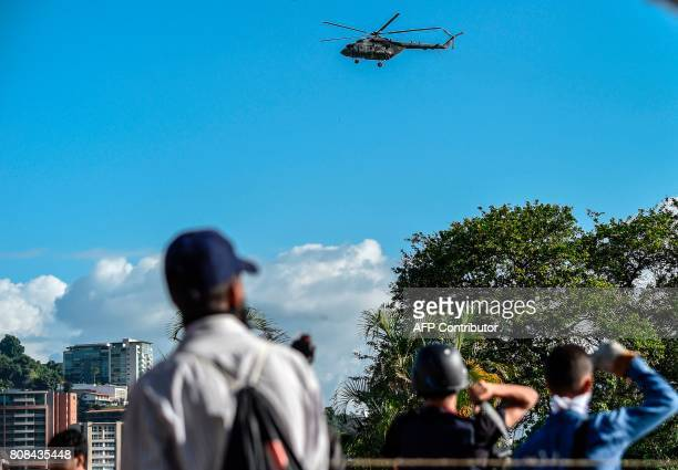 A Venezuelan Russianmade Mi17 helicopter overflies the city during an antigovernment protest in Caracas on July 4 2017 / AFP PHOTO / JUAN BARRETO