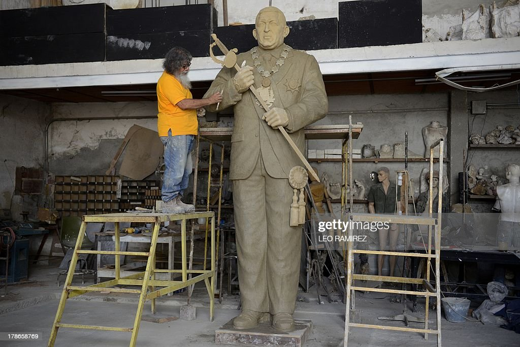 Venezuelan sculptor Julio Briceno, 63, works on a 3.20 meter-high statue of late Venezuelan former President Hugo Chavez at his workshop in Guatire, outskirts of Caracas on August 26, 2013. Commissioned by a local governor, the statue hasn't a defined emplacement yet. Nearly six month of his death, the image of Chavez still appears in buildings and corners of the country. AFP PHOTO/Leo RAMIREZ