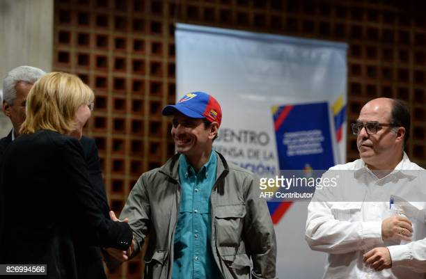 Venezuelan senior opposition leader Henrique Capriles shakes hands with dismissed chief prosecutor Luisa Ortega as the leader of the...