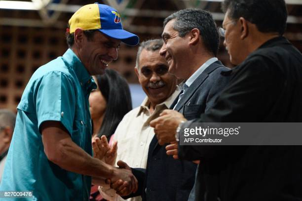 Venezuelan senior opposition leader Henrique Capriles shakes hands with former Interior and Justice Minister Miguel Rodriguez Torres during the 'In...