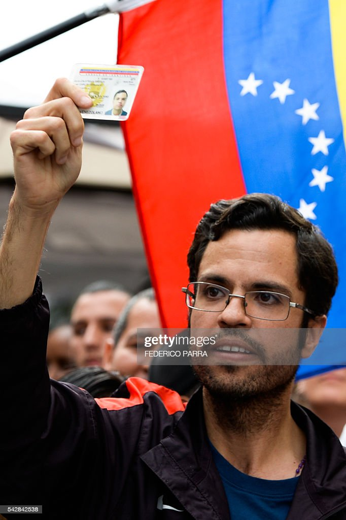 A Venezuelan shows his ID card during a spontaneous demonstration after the closure of centres to authenticate their signatures for a recall referendum against Venezuelan President Nicolas Maduro, in front of the National Electoral Council (CNE) in Caracas, on June 24, 2016. Soaring crime, runaway inflation and a sharply contracting economy, worsened by falling oil prices, have fueled a drive for a recall referendum to remove Maduro, as a way out of the crisis. / AFP / FEDERICO