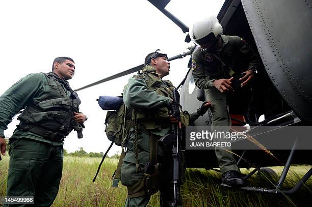 A Venezuelan soldier speaks with the crew of a helicopter during an operation to destroy clandestine airstrip used by drug traffickers in Apure 45km...