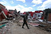 A Venezuelan soldier walks next to rubble after the houses of illegal Colombian immigrants were destroyed during an operation in the border city of...