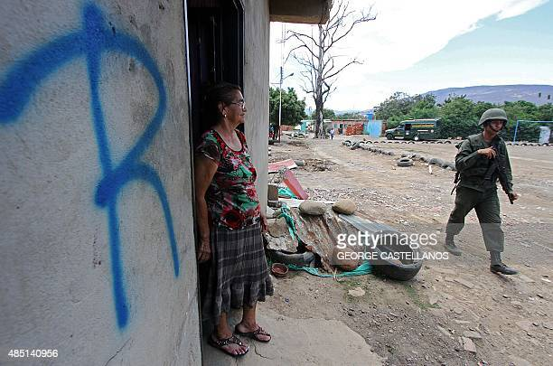 A Venezuelan soldier walks past a woman who remains at her housed marked with an 'R' of 'Revisado' during an operation in search of illegal Colombian...
