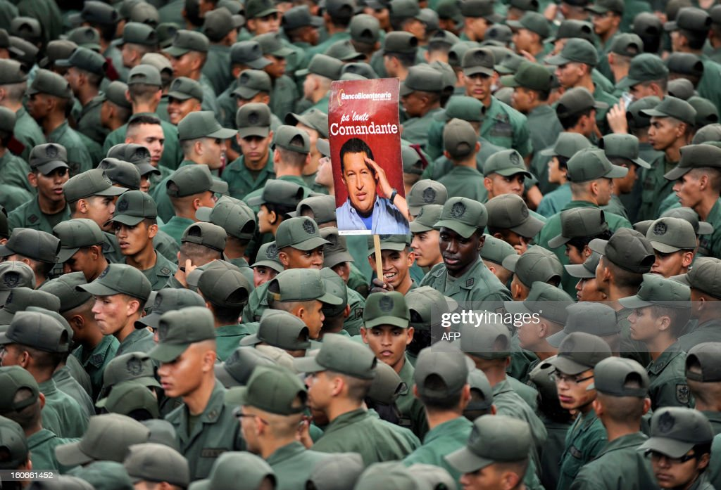 Venezuelan soldiers hold a poster of Venezuelan President Hugo Chavez during the conmemoration of the 1992 failed coup led by Hugo Chavez, who was an army lieutenant colonel, against then president Carlos Andres Perez, in Caracas, on February 4, 2013. Ailing President Hugo Chavez, who had cancer surgery in December, is doing much better and recovering, Cuban leader Fidel Castro said in remarks published Monday. AFP PHOTO/Leo RAMIREZ AFP PHOTO/ Leo RAMIREZ