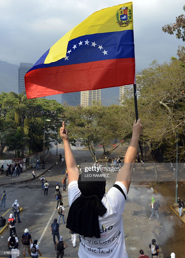 A Venezuelan student waves a national flag during a protest against the government of President Nicolas Maduro, in Caracas on March 12, 2014. A young man was shot dead in a confused event during protests in the city of Valencia, in northern Venezuela. About 3,000 Venezuelan students marched Wednesday to mark a month since the first deaths in anti-government protests that have now claimed at least 22 lives.