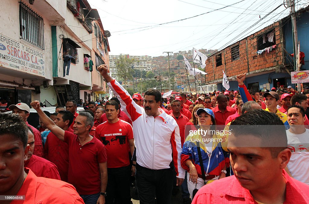 Venezuelan Vice President Nicolas Maduro (C-white shirt) and suporters of Venezuelan President Hugo Chavez rally during the commemoration of the 55th anniversary of the end of the dictatorship (1952-1958) of Marcos Perez Jimenez in Caracas on January 23, 2013. Thousands of Venezuelans marched in support of cancer-stricken President Hugo Chavez in Caracas Wednesday on the anniversary of the day the country's last dictator was overthrown. AFP PHOTO/JUAN BARRETO.