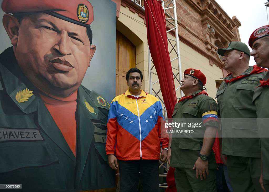 Venezuelan Vice President Nicolas Maduro, the president of the National Assembly, Diosdado Cabello and Venezuelan Minister of Defense Diego Molero Bellavia, stand next to a huge portrait of Venezuelan President Hugo Chavez during the conmemoration of the 1992 failed coup led by Chavez, who was an army lieutenant colonel, against then president Carlos Andres Perez, in Caracas, on February 4, 2013. Ailing President Hugo Chavez, who had cancer surgery in December, is doing much better and recovering, Cuban leader Fidel Castro said in remarks published Monday. AFP PHOTO/Juan BARRETO