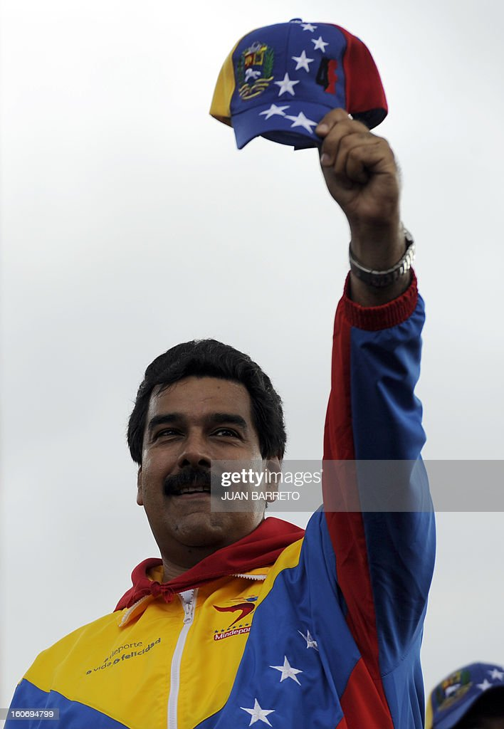 Venezuelan Vice President Nicolas Maduro waves during the conmemoration of the 1992 failed coup led by Chavez, who was an army lieutenant colonel, against then president Carlos Andres Perez, in Caracas, on February 4, 2013. Ailing President Hugo Chavez, who had cancer surgery in December, is doing much better and recovering, Cuban leader Fidel Castro said in remarks published Monday. AFP PHOTO/Juan BARRETO