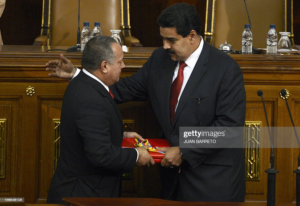 Venezuelan Vice-President Nicolas Maduro (R) approaches to embrace the president of the National Assembly Diosdado Cabello after handing the ledger of the country to him in Caracas on January 15, 2013. AFP PHOTO