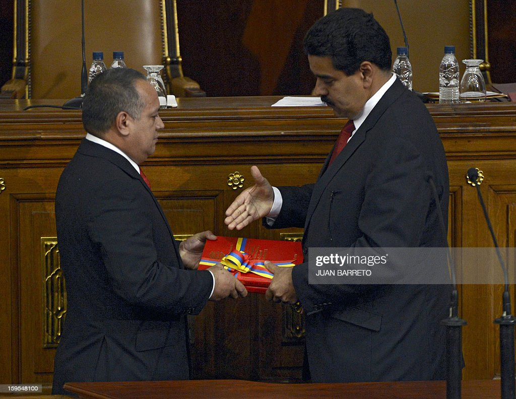 Venezuelan Vice-President Nicolas Maduro (R) hands in the ledger of the country to the president of the National Assembly Diosdado Cabello in Caracas on January 15, 2013. AFP PHOTO
