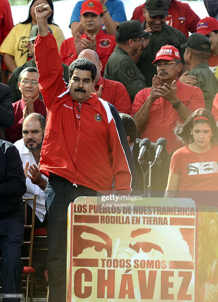 Venezuelan Vice-President Nicolas Maduro raises his fist as he delivers a speech during a massive gathering in homage of Venezuelan President Hugo Chavez in front of Miraflores presidential palace in Caracas on January 10, 2013. With cancer-stricken President Hugo Chavez hospitalized in Cuba, thousands of flag-waving Venezuelans in red shirts filled the streets of Caracas Thursday to inaugurate his new term without him. Bands played anthems from street-side stages as people poured out of buses to make their way on foot toward the Miraflores presidential palace for a symbolic swearing-in of the people in place of Chavez, who is too sick to take the oath of office. AFP PHOTO/Juan BARRETO