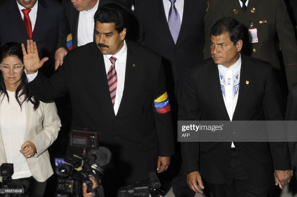 Venezuelan Vice-President Nicolas Maduro (C) waves next to his wife Cilia Flores (L) and Ecuadorean President Rafael Correa (R) as they enter the National Assembly in Caracas on March 8, 2013. Latin American leaders and US foes paid tribute to Venezuelan leader Hugo Chavez on Friday as he lay in state in a flag-draped coffin during a lavish state funeral before the nation swears-in an interim president. AFP PHOTO/ Leo RAMIREZ