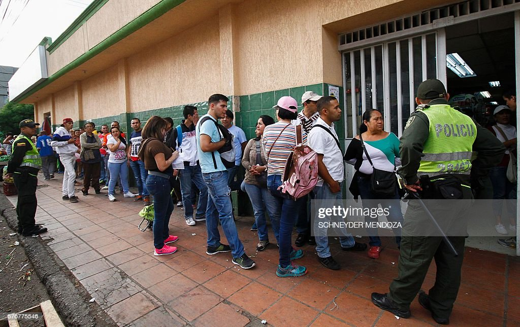 Venezuelans line up to buy at a supermarket in Cucuta Colombia on July 17 2016 Thousands of Venezuelans crossed the border with Colombia to take...