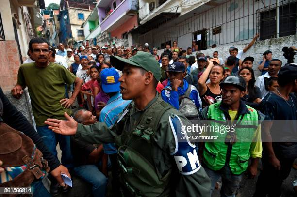 TOPSHOT Venezuelans queue outside a polling station as they wait to cast their vote during regional elections in Caracas Venezuela on October 15 2017...