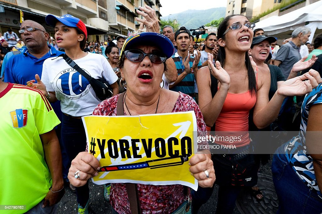 Venezuelans shout slogan after the closure of centres to authenticate their signatures for a recall referendum before the National Electoral Council (CNE) in Caracas, on June 24, 2016. Soaring crime, runaway inflation and a sharply contracting economy, worsened by falling oil prices, have fueled a drive for a recall referendum to remove Maduro, as a way out of the crisis. / AFP / FEDERICO