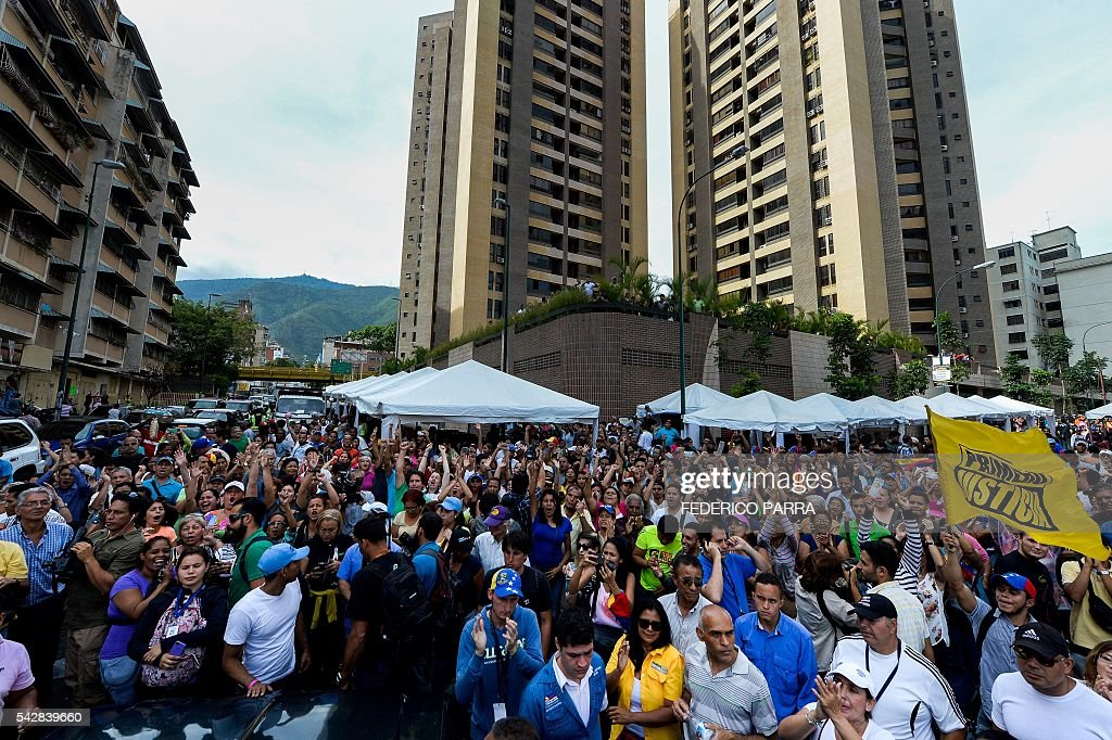 Venezuelans shout slogan during a spontaneous demonstration after the closure of centres to authenticate their signatures for a recall referendum before the National Electoral Council (CNE) in Caracas, on June 24, 2016. Soaring crime, runaway inflation and a sharply contracting economy, worsened by falling oil prices, have fueled a drive for a recall referendum to remove Maduro, as a way out of the crisis. / AFP / FEDERICO