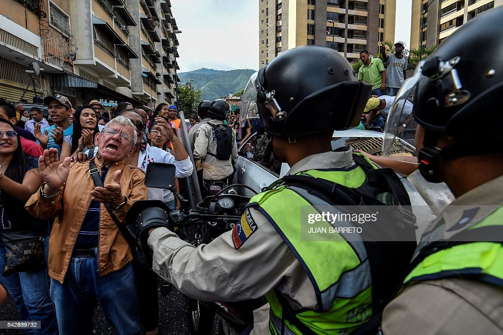 Venezuelans shout slogan in front on members of the national police during a spontaneous demonstration after the closure of centres to authenticate their signatures for a recall referendum before the National Electoral Council (CNE) in Caracas, on June 24, 2016. Soaring crime, runaway inflation and a sharply contracting economy, worsened by falling oil prices, have fueled a drive for a recall referendum to remove Maduro, as a way out of the crisis. / AFP / FEDERICO