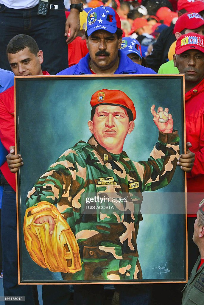 Venezuela's acting President Nicolas Maduro holds a picture of the late president Hugo Chavez during a campaign rally in Catia la mar, state of Vargas on April 9, 2013. Venezuelans will elect new president next April 14 and the final stretch of Venezuela's race to replace Hugo Chavez coincides with a delicate anniversary for the opposition: 11 years since a brief coup against the late leftist leader. AFP PHOTO/Luis Acosta