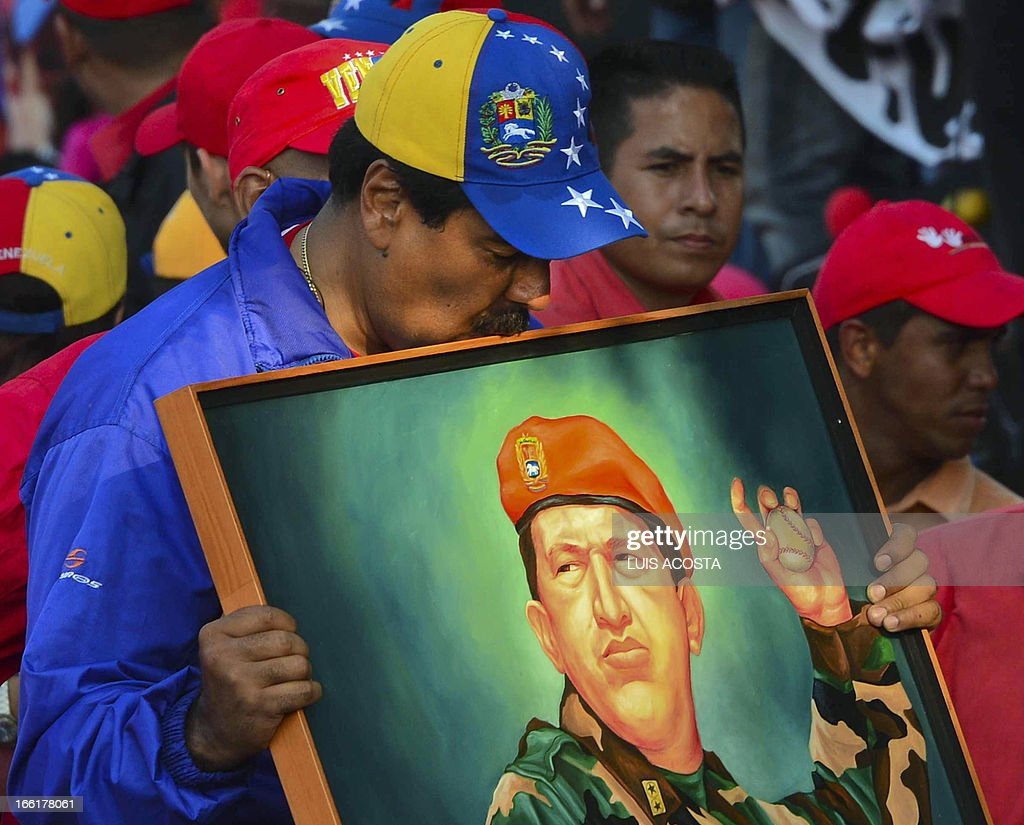 Venezuela's acting President Nicolas Maduro kisses a picture of the late president Hugo Chavez during a campaign rally in Catia la mar, state of Vargas on April 9, 2013. Venezuelans will elect new president next April 14 and the final stretch of Venezuela's race to replace Hugo Chavez coincides with a delicate anniversary for the opposition: 11 years since a brief coup against the late leftist leader. AFP PHOTO/Luis Acosta