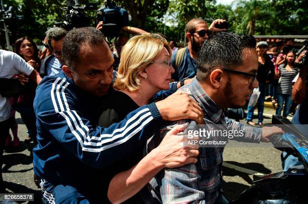 Venezuela's chief prosecutor Luisa Ortega one of President Nicolas Maduro's most vocal critics is driven away on a motorbike after a flash visit to...