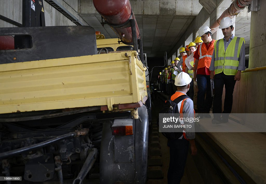 Venezuela's Deputy Foreign Minister Tamir Porras (2nd R) and French Junior Minister for the Social Economy, Benoit Hamon (R) walk during a visit to subway stations' construction works by French company Alstom, in Caracas on November 25, 2012. Venezuela and France signed seven cooperation agreements in areas such as manufacturing, mining, science and tourism during Hamon's visit to Caracas.