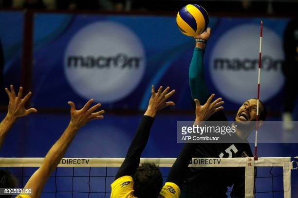 Venezuela's Emerson Rodriguez spikes the ball to score over Brazil's Bruno Rezende and Lucas Saatkamp during their Men's South American Volleyball...
