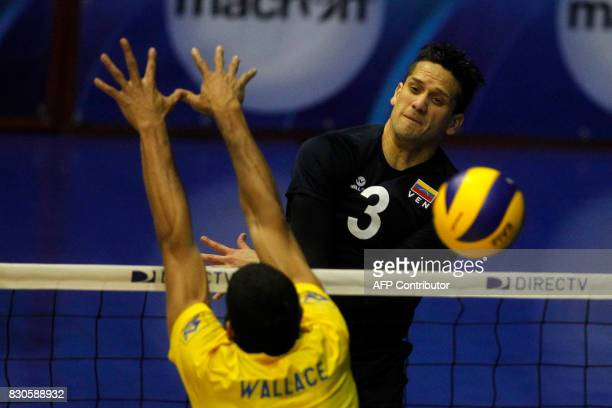Venezuela's Fernando Gonzalez spikes the ball to score over Brazil's Wallace Souza during their Men's South American Volleyball Championship final in...