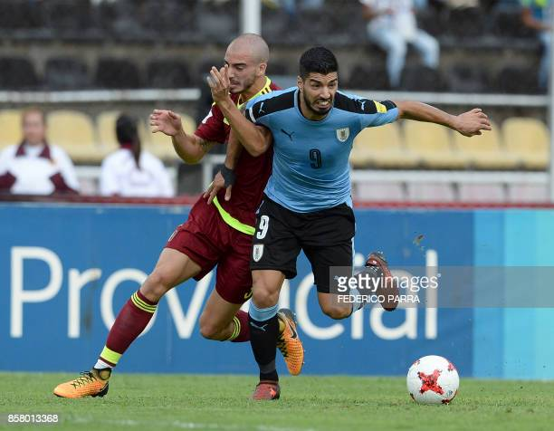 Venezuela's Mikel Villanueva and Uruguay's Luis Suarez vie for the ball during their 2018 World Cup qualifier football match in San Cristobal...